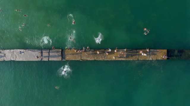 People swimming jumping from the pier to the water. Aerial conceptual video from top - video