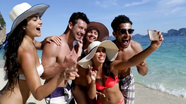 people take selfie photo on cell smart phone on beach, happy smiling young tourists group on vacation - spanish and portuguese ethnicity stock videos & royalty-free footage