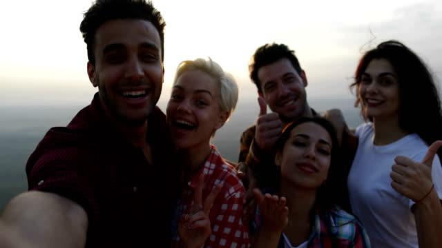 menschen nehmen selfie foto auf berg bei sonnenaufgang, mix race freundesgruppe touristen senden schlag küsse - gebirge stock-videos und b-roll-filmmaterial