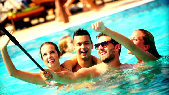 People taking selfies at swimming pool. Group of friends taking selfies at swimming pool They are using waterproof camera attached to selfies stick. There are two guys and two girls. pool party stock videos & royalty-free footage
