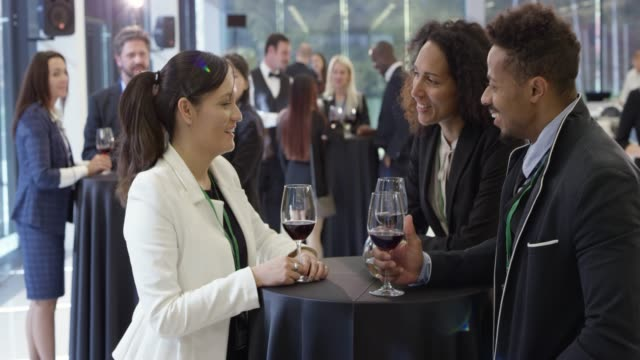 People talking and drinking a glass of wine in the lobby of a conference center
