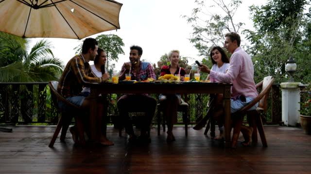 Gente que habla sentado en la mesa al aire libre comiendo en grupo de amigos de jóvenes terraza feliz sonriendo comunicación - vídeo