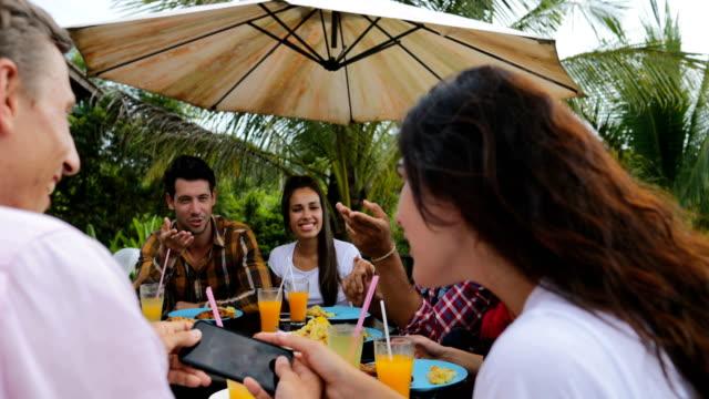 Gente que habla sentado en la mesa al aire libre comiendo en grupo de amigos de jóvenes terraza feliz sonriendo Closeup comunicación - vídeo