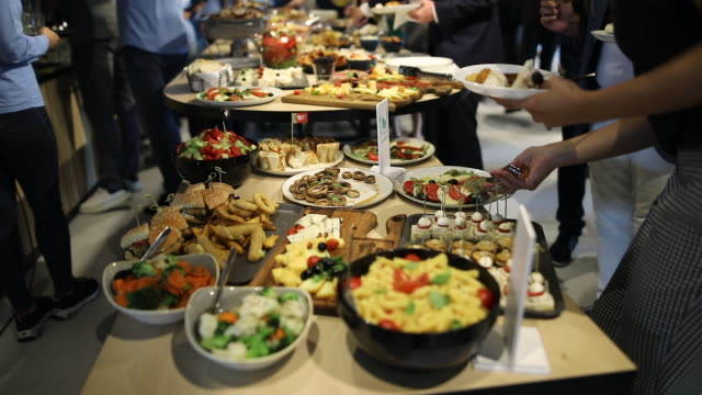 People tasting vegetarian food after opening ceremony. Young female person putting food from table in her plate during buffet