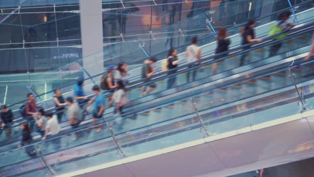 ショッピング モール内、エスカレーターで移動する人々 - 展示会点の映像素材/bロール