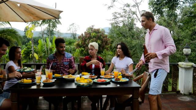 Vasos de jugo tostado sentado en la mesa en terraza comer a jóvenes amigos hablando al aire libre comunicación de la gente - vídeo