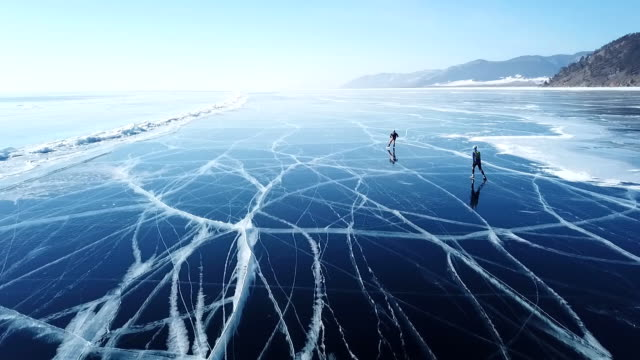 vídeos de stock e filmes b-roll de people tourist walk go on smooth surface. picturesque lake baikal cracks blue glossy clear ice hummocks snow snowdrifts. best north russia asia. winter sunny day blue sky. aerial approach. - lago baikal