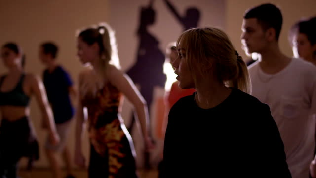 People training to dance in the studio Young people are dancing in the studio together. The dancers have a dance rehearsal and training to perform modern style of dance. Attractive guys and girls looks on trainer and repeat after him. dance studio stock videos & royalty-free footage