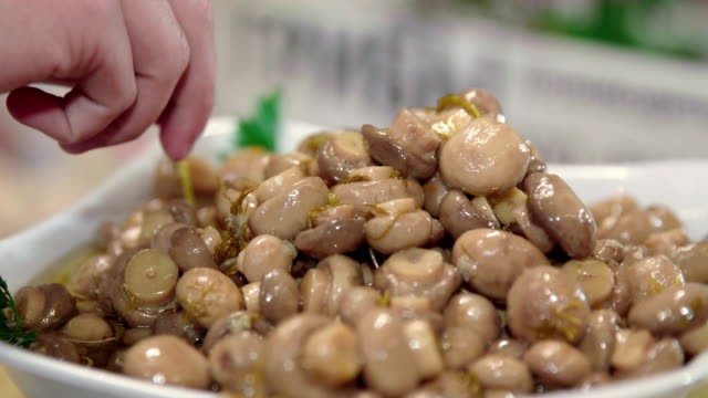People trying Pickled mushrooms on formal reception video