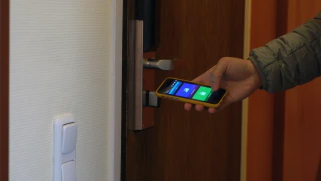 人々 はドアを制御するのにスマート フォンを使用します。スマート ホームとホーム オートメーション技術 - モノのインターネット点の映像素材/bロール