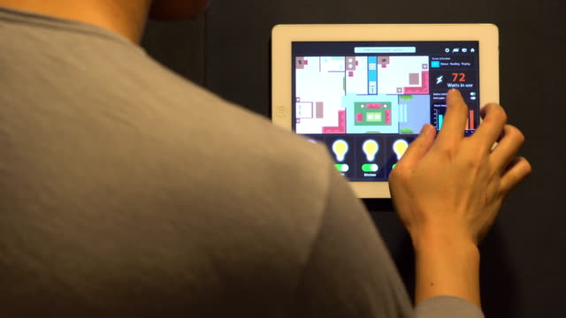 People use tablet to control the light. Smart home and home automation technology