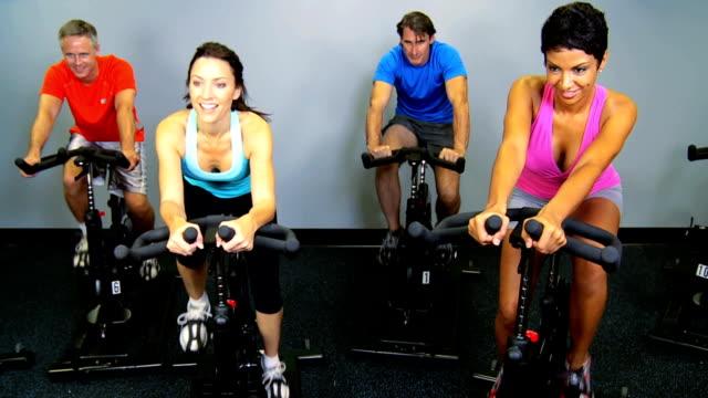 名様のヘルスクラブのサイクリングマシンを使用 - 人の筋肉点の映像素材/bロール