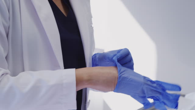People Beautician or doctor putting on latex gloves and preparing syringe before anti ageing Injection - shot in slow motion surgical equipment stock videos & royalty-free footage