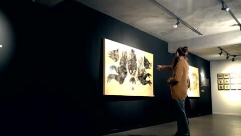 vídeos de stock e filmes b-roll de people visit an exhibition - arte