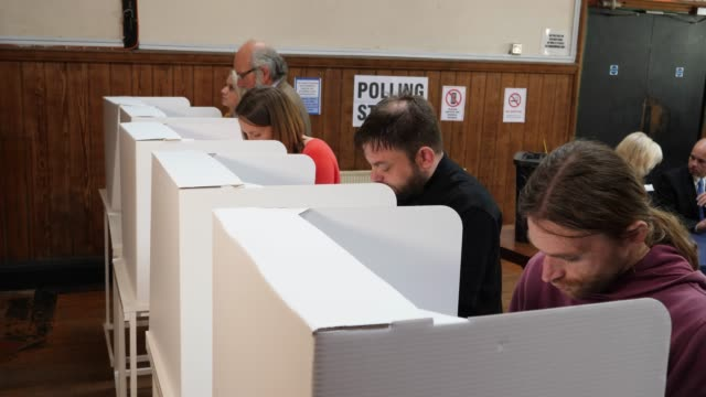 4k: people voting in polling booths at the election - voting at polling place - democrazia video stock e b–roll