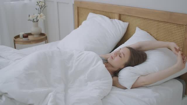 människor som vaknar upp - ung kvinna öppnar ögonen på en solig morgon. flickan ligger i sängen, vaknar och sött sträcker sig. - duntäcke bildbanksvideor och videomaterial från bakom kulisserna