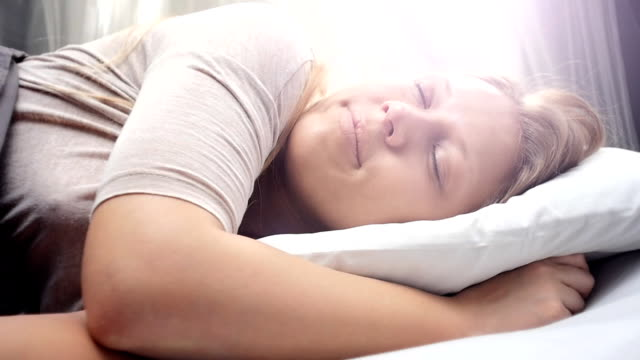 People waking up - Young woman opens her eyes on a sunny morning video