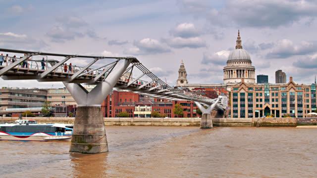 la gente attraversa il ponte milllenio. chiesa in lontananza. traghetto in acqua. londra. - london bridge inghilterra video stock e b–roll