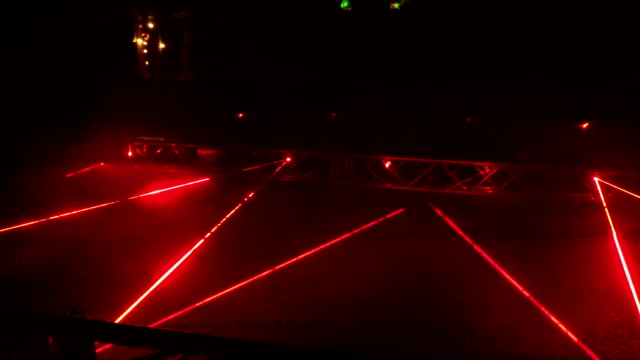 People walk laser formed red lines night light show. 4K