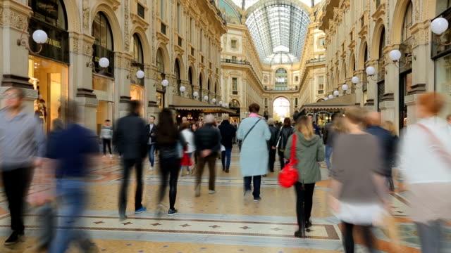 people walk on duomo square near the famous vittorio emanuele shopping gallery, milan city, italy. - alta moda italy video stock e b–roll