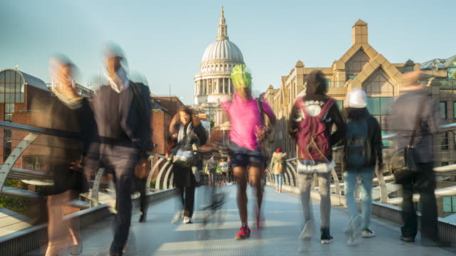 People walking across Millenium Bridge with St Paul's Cathederal in the background