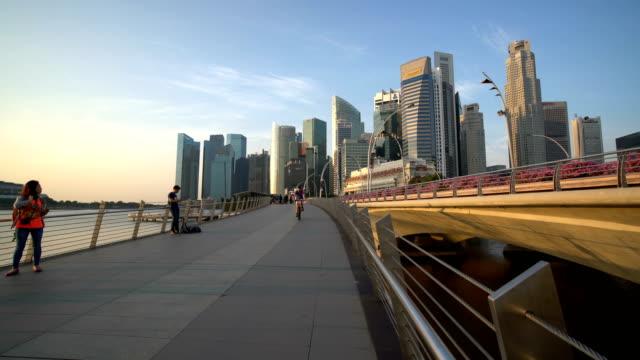 Personas a pie y en bicicleta en Marina Bay, Singapur con fondo de rascacielos - vídeo