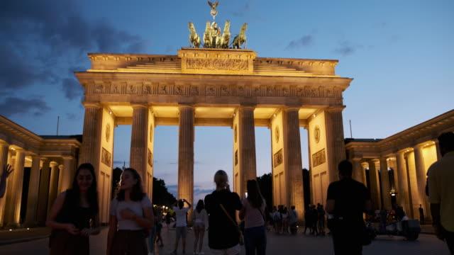 vídeos y material grabado en eventos de stock de personas caminando por la puerta de brandenburgo, alemania por la noche - stabilized shot