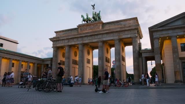 vídeos y material grabado en eventos de stock de personas caminando por la puerta de brandenburgo, alemania al atardecer - stabilized shot