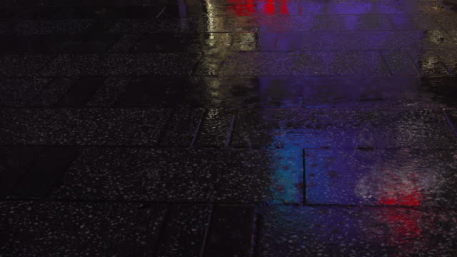 People walking at night on a sidewalk during a rainy day.