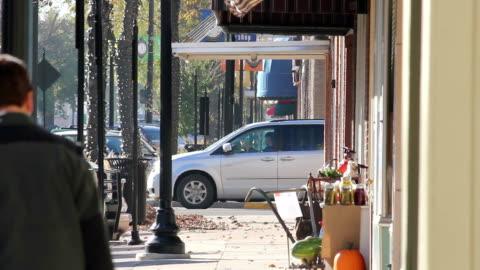 vídeos y material grabado en eventos de stock de gente caminando por la calle principal de la ciudad pequeña - calle principal calle
