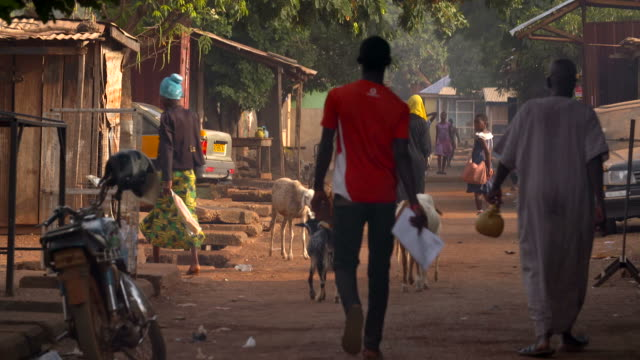 people walking down the street in ghana small village street in ghana, west africa poverty stock videos & royalty-free footage