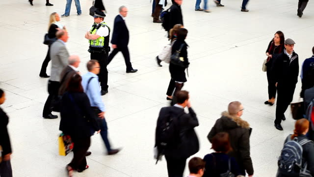 People Walking In A London Station Watched By Policeman