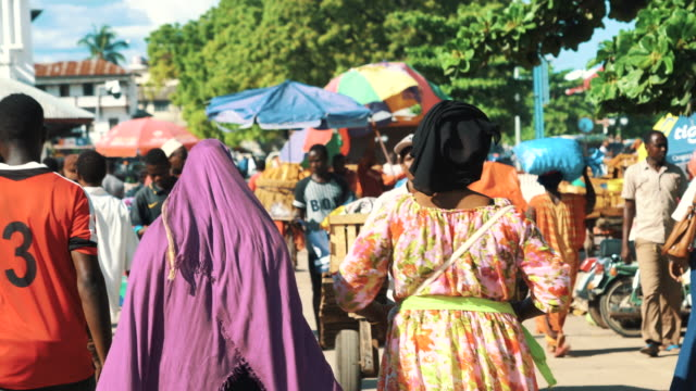 People walking in crowded market street of Stone Town, Zanzibar, Tanzania