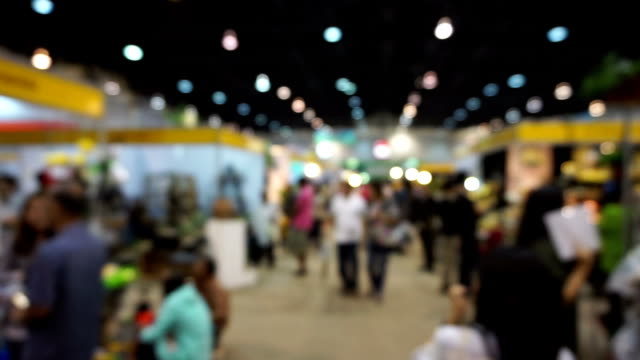 People walking in exhibition fair defocused background. video
