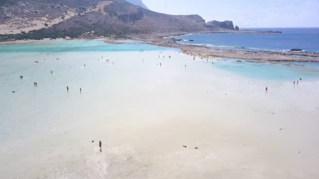 People walking in shalow water of Balos lagoon On the far northwest corner of Crete—is one of the most picturesque locales in the entire Mediterranean greek islands stock videos & royalty-free footage