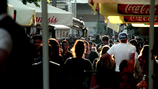 people walking in the city in a summer sunset: crowd walking, restaurant, shops video