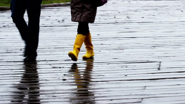 People walking in the rain on a wooden embankment, gloomy video