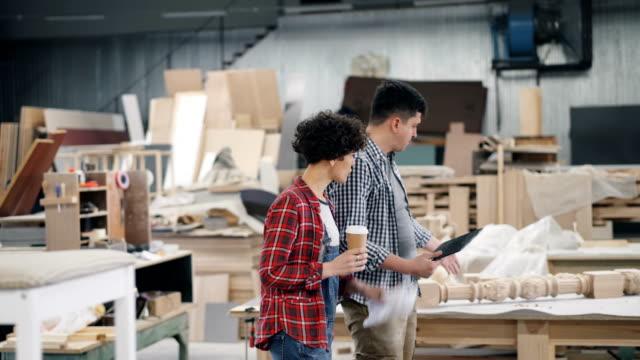 menschen, die in der werkstatt sprechen und über die arbeit sprechen, die kaffee und tablet hält - tischlerarbeit stock-videos und b-roll-filmmaterial