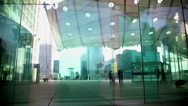 people walking near creative glass entrance in skyscraper, modern architecture - city walking background video stock e b–roll
