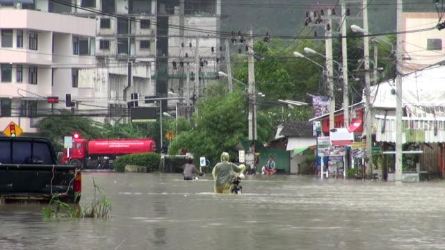 People walking on flooded street People walking on street under flood in Phuket Thailand rescue worker stock videos & royalty-free footage