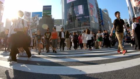 4k persone che camminano sulla strada di attraversamento di shibuya. - people video stock e b–roll