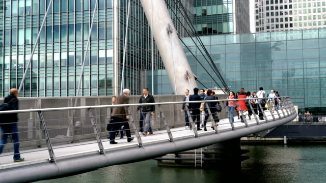 People walking on South Quay Footbridge, Canary Wharf, London UK People walking on South Quay Footbridge, Canary Wharf, London UK office park stock videos & royalty-free footage