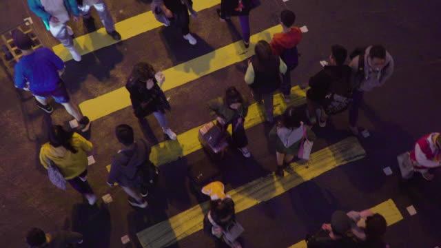 people walking on zebra cross in night time - центральный район стоковые видео и кадры b-roll