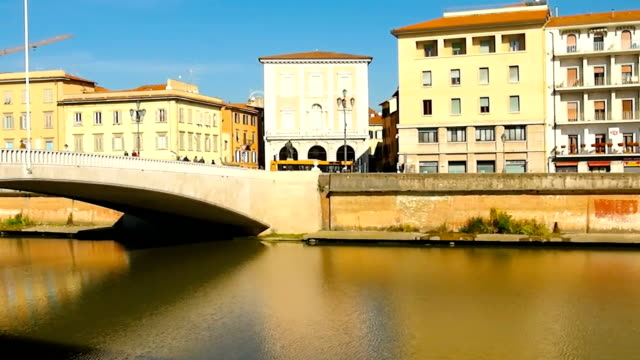 people walking over a bridge across arno river - pisa stok videoları ve detay görüntü çekimi