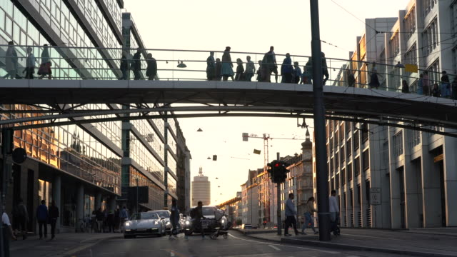 People walking over bridge in Munich, Germany at sunset