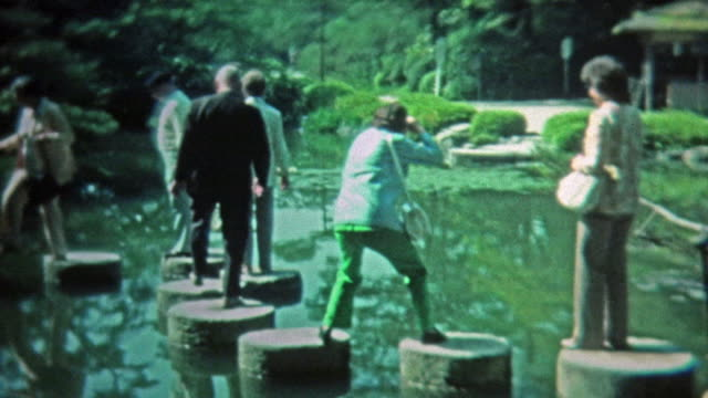 1972: People walking the stepping stones around the zen Japanese style pond. video