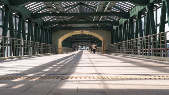 People walking through a Steel pedestrian crossing from the residential areas to the Park, over the railroad tracks and the freeway, time lapse