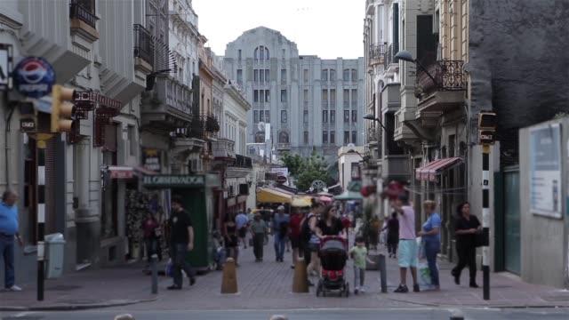 People Walking Through An Old Street In Montevideo (Uruguay).