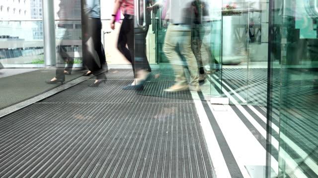 люди ходить через современные здания входной двери, time lapse. - вход стоковые видео и кадры b-roll