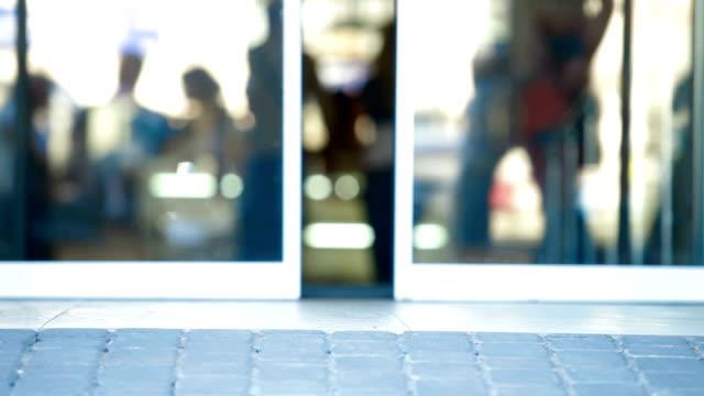 People Walking Through The Glass Doors